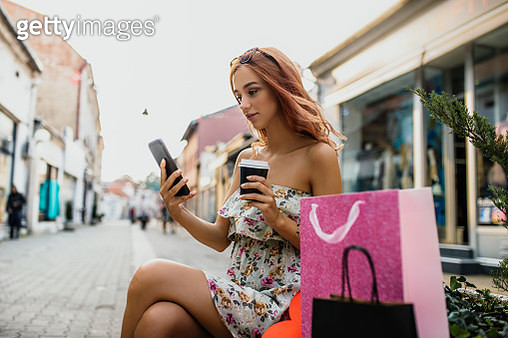 Beautiful girl sits on the bench and rests after a successful shopping - gettyimageskorea