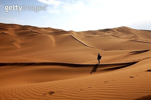 Man Standing On Sand Dunes At Desert Against Sky - gettyimageskorea