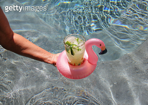 Serving a drink at the pool in a pink flamingo float - gettyimageskorea