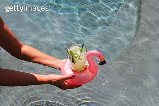 Swimming pool with drink served in a pink flamingo float coaster - gettyimageskorea