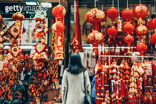 Rear view of woman standing against various Chinese New Year decorations and ornaments on city street - gettyimageskorea