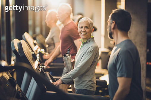 Four athletic seniors walking on treadmills in a gym and communicating. - gettyimageskorea