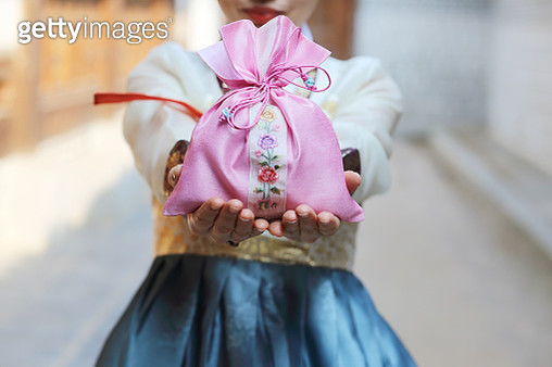 Woman in Korean traditional clothes with lucky bag - gettyimageskorea