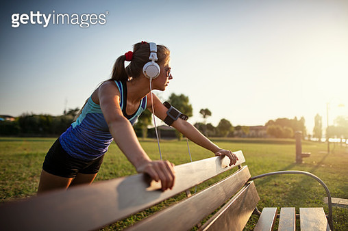 Teenage girl jogging in park on sunset. The girl is doing some stretching on park bench.Sunny summer day sunset.Nikon D850 - gettyimageskorea