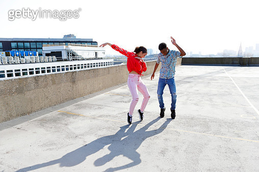 Teenagers dancing on a London rooftop overlooking the city. - gettyimageskorea