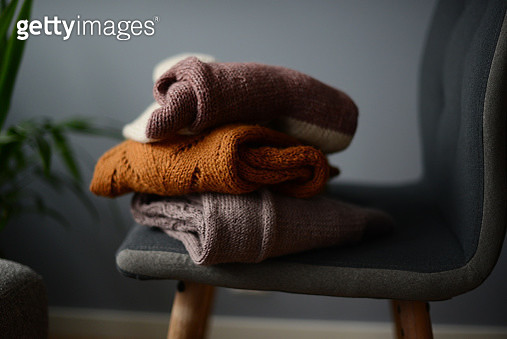 three knitted sweaters on a chair by a green plant - gettyimageskorea