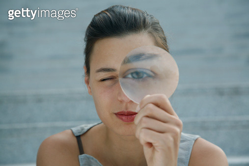 Woman looking through magnifying glass - gettyimageskorea