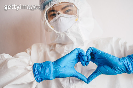 Healthcare worker doing heart hand sign while wearing PPE suit for working in hospital. - gettyimageskorea