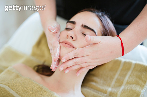 Young woman receiving facial beauty treatment in a spa - gettyimageskorea