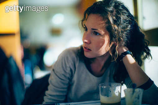 Portrait of concerned young woman looking away in the coffee shop. - gettyimageskorea