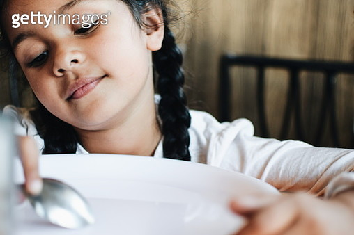 Close-Up Of Girl Looking Down With Spoon And Plate At Home - gettyimageskorea