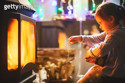 Little girl sitting near fireplace with Christmas decoration - gettyimageskorea