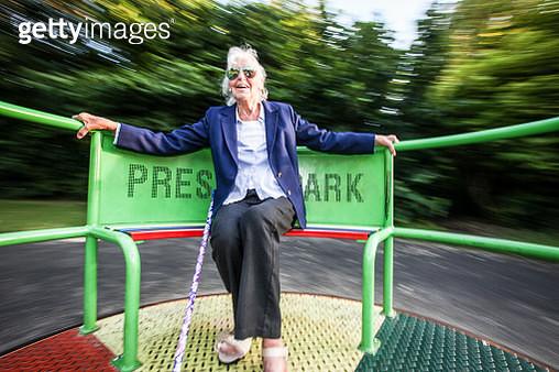 Senior lady enjoying playground ride - gettyimageskorea