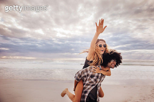 Boho Girl Rides Piggyback on hipster Man at Beach - gettyimageskorea