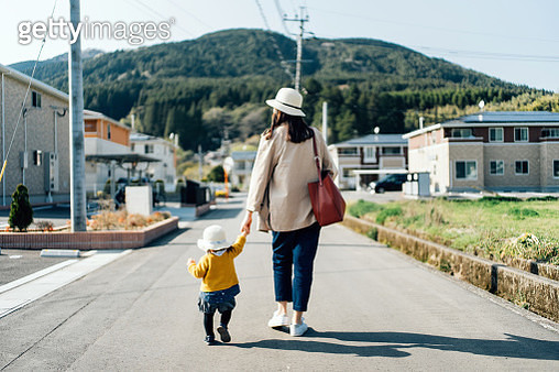 Mother and daughter with straw hat holding hands walking along town in the countryside on a sunny day - gettyimageskorea