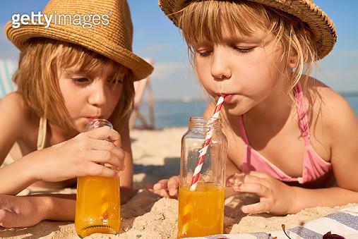 Kids Drinking Juice On Beach - gettyimageskorea