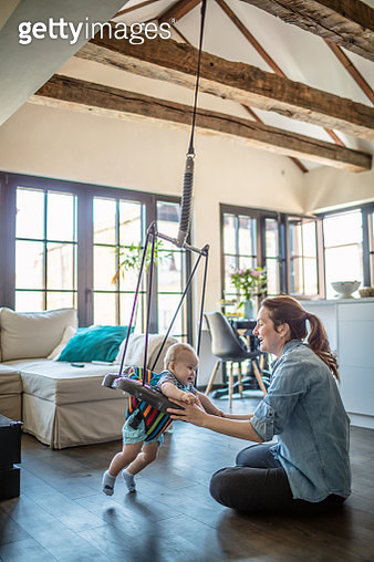 Mom swings her little baby at home - gettyimageskorea