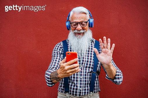 Handsome well dressed senior man with gray beard and hair having video call on smartphone while leaning on red wall. - gettyimageskorea