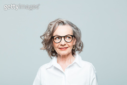 Elderly lady wearing white shirt and glasses standing against grey background, looking away and smiling. Studio shot of female designer. - gettyimageskorea