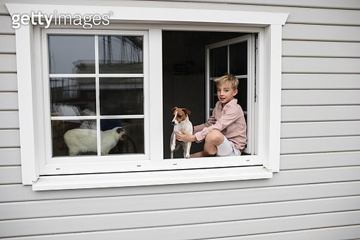 Portrait of boy sitting on window sill with Jack Russel Terrier and Siam cat looking out of open window - gettyimageskorea