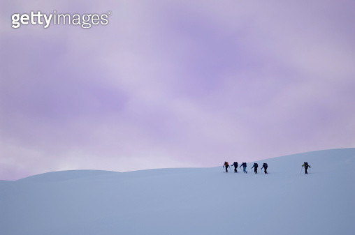 Group of people climbing in snow, side view - gettyimageskorea