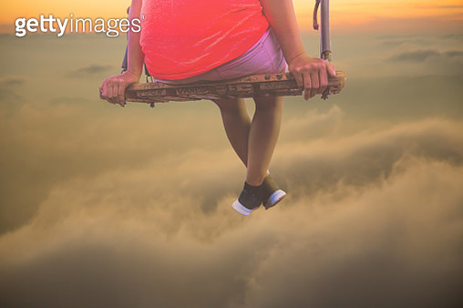Dreamlike picture of relaxed woman on swing over the clouds in a surreal picture. - gettyimageskorea