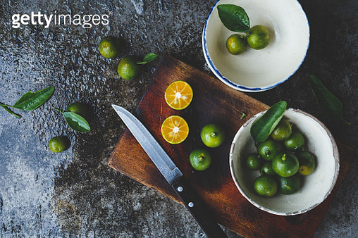 Directly Above Shot Of Kumquats In Bowls With Knife On Kitchen Counter - gettyimageskorea