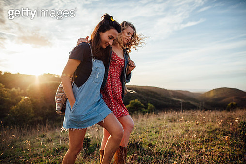 Two young women walking together in sunshine - gettyimageskorea