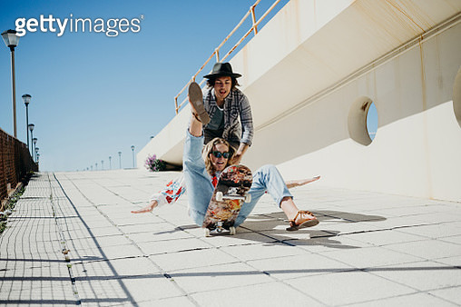 Young woman falling off skateboard while being pushed by young man - gettyimageskorea