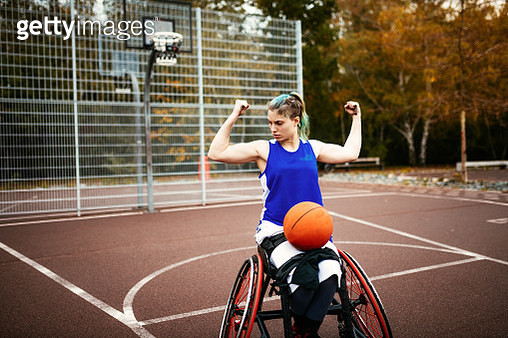 Muscular woman in wheelchair showing biceps muscles with basketball ball in her lap - disability sport and recreation - gettyimageskorea