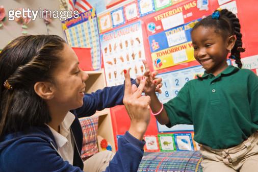 Teacher showing pre-school girl sign language - gettyimageskorea
