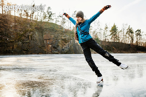 An amateur ice skater posing with her arms in the air while skating on a frozen lake. - gettyimageskorea