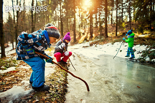 Children playing with a frozen puddle in winter - gettyimageskorea