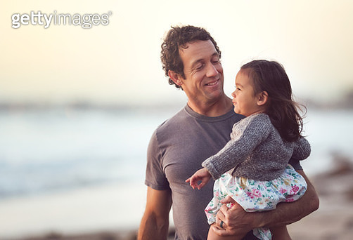 A handsome middle aged dad holds his mixed race daughter during a walk on the beach. - gettyimageskorea