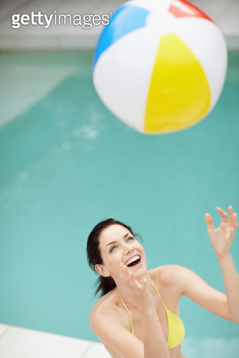 Attractive brunette playing with a beach ball - gettyimageskorea