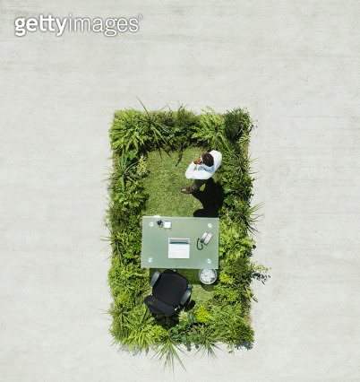 Businessman and desk on lush lawn in cement courtyard - gettyimageskorea