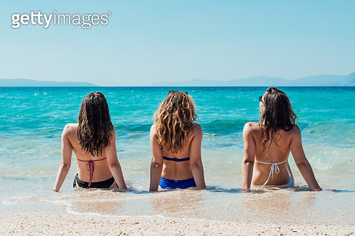 Rear View Of Female Friends Sitting On Shore At Beach - gettyimageskorea