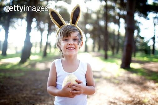 Little boy in forest holding golden Easter egg - gettyimageskorea
