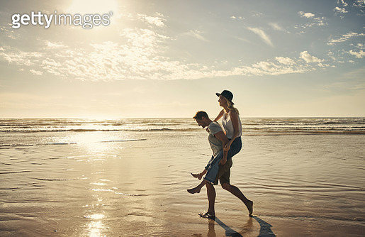 Shot of a young couple enjoying a piggyback ride at the beach - gettyimageskorea