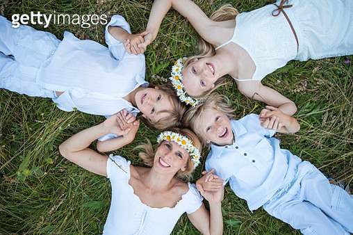 Family with mother lying on the grass looking up into the camera. Hippie style with chamonmile floral garland on females heads. - gettyimageskorea