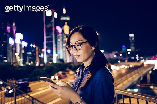 Businesswoman using smartphone in city at night - gettyimageskorea