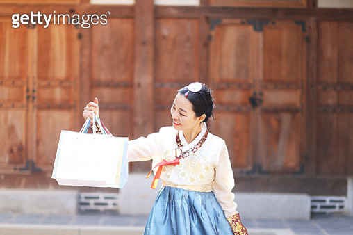 Woman wearing Korean traditional clothes with shopping bags - gettyimageskorea