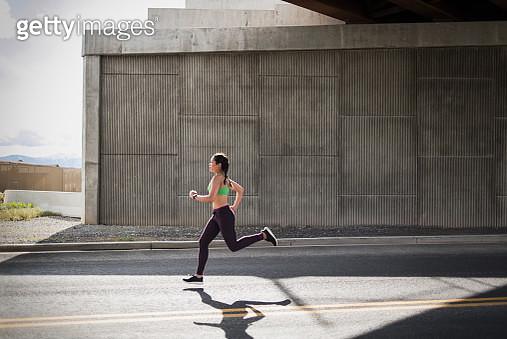 Young woman running under freeway overpass - gettyimageskorea