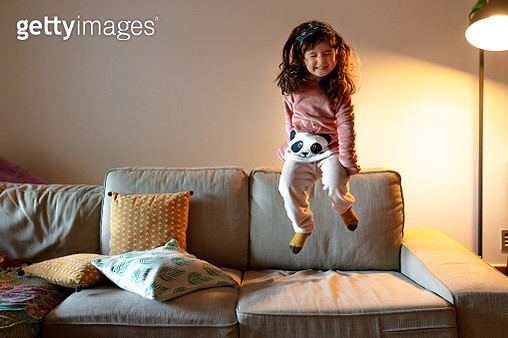 Happy four years old little girl jumping on the couch on pajamas - gettyimageskorea
