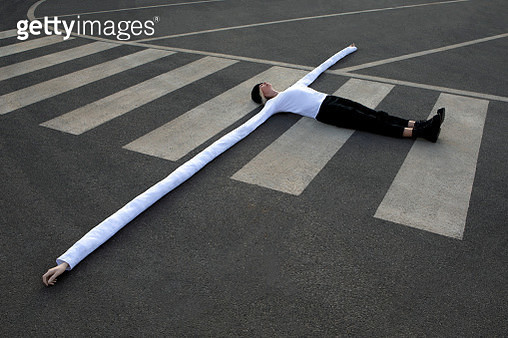 Woman with long artificial hands lying on crosswalk - gettyimageskorea