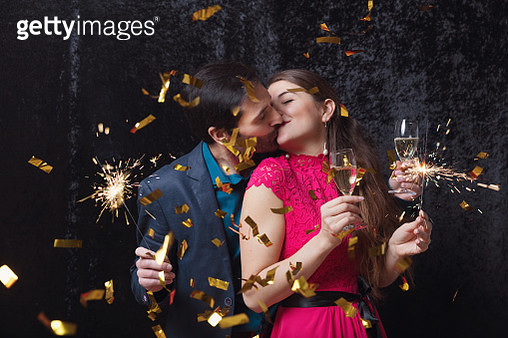 Beautiful couple celebrating New Year's Eve with sparkler - gettyimageskorea