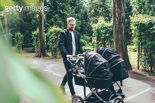 Full length of man pushing baby carriage on footpath - gettyimageskorea