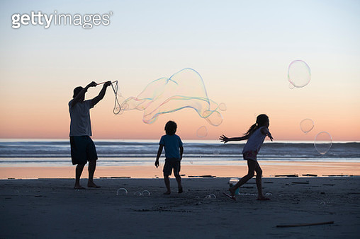 Silouette of family playing on the beach at sunset - gettyimageskorea