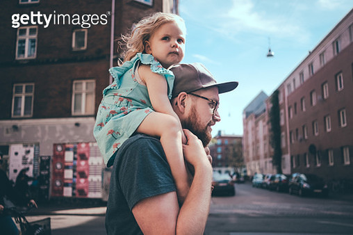 Side view of father carrying daughter on shoulders at city street - gettyimageskorea