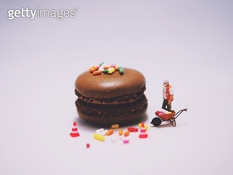 Close-Up Of Macaroon By Figurine Over White Background - gettyimageskorea
